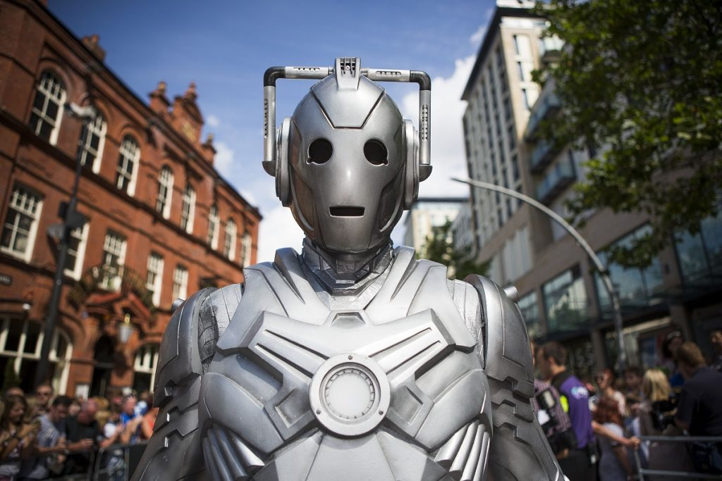A silver cyborg in a crowd. The Tesla Cybertruck and Doctor Who Cybermen are eerily similar.