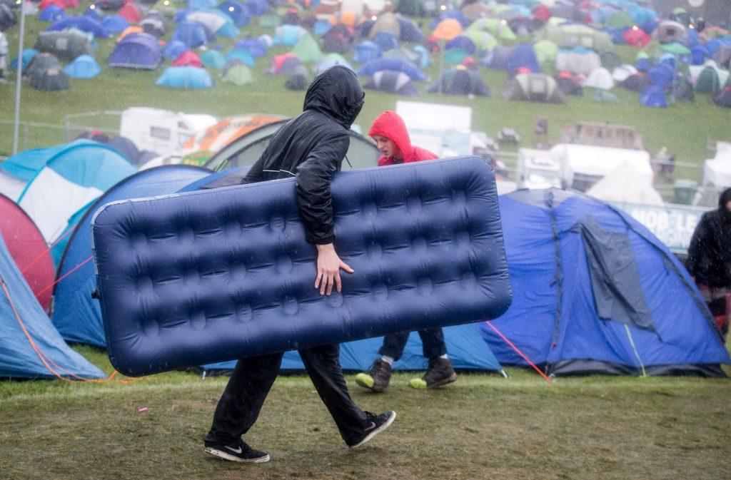 A man carrying an air mattress into a festival as it rains