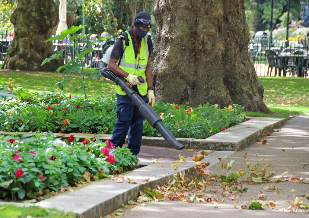 A city work in a yellow vest operating a leaf blower