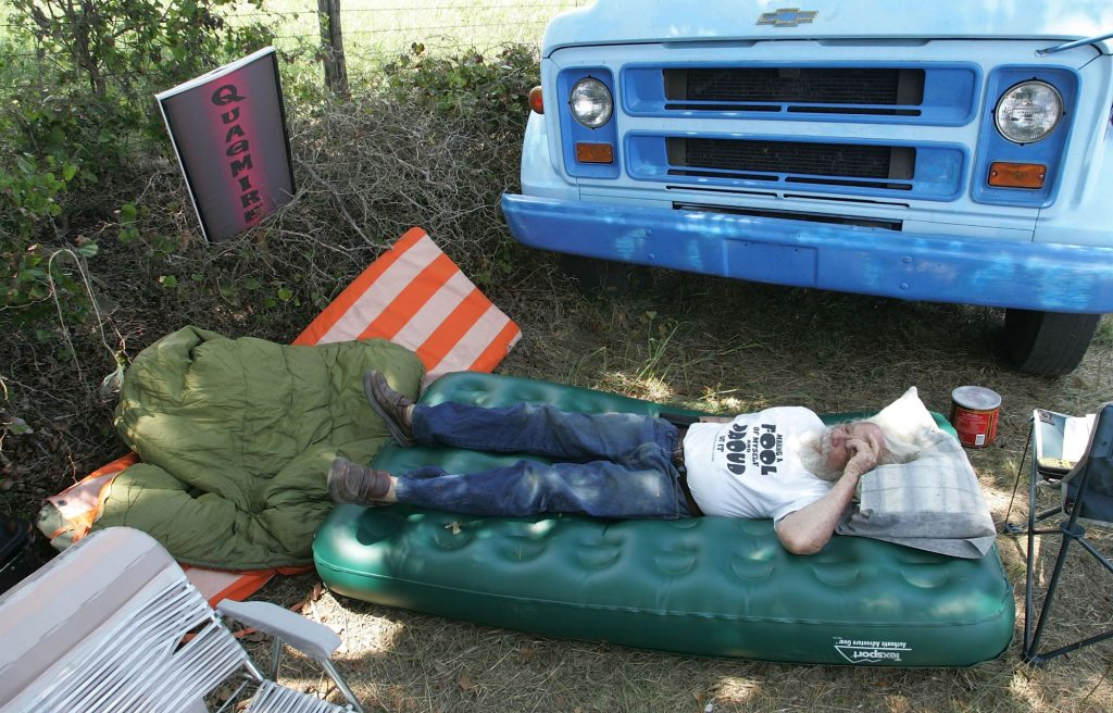 A man lying on an air mattress outside of his Chevy vehicle