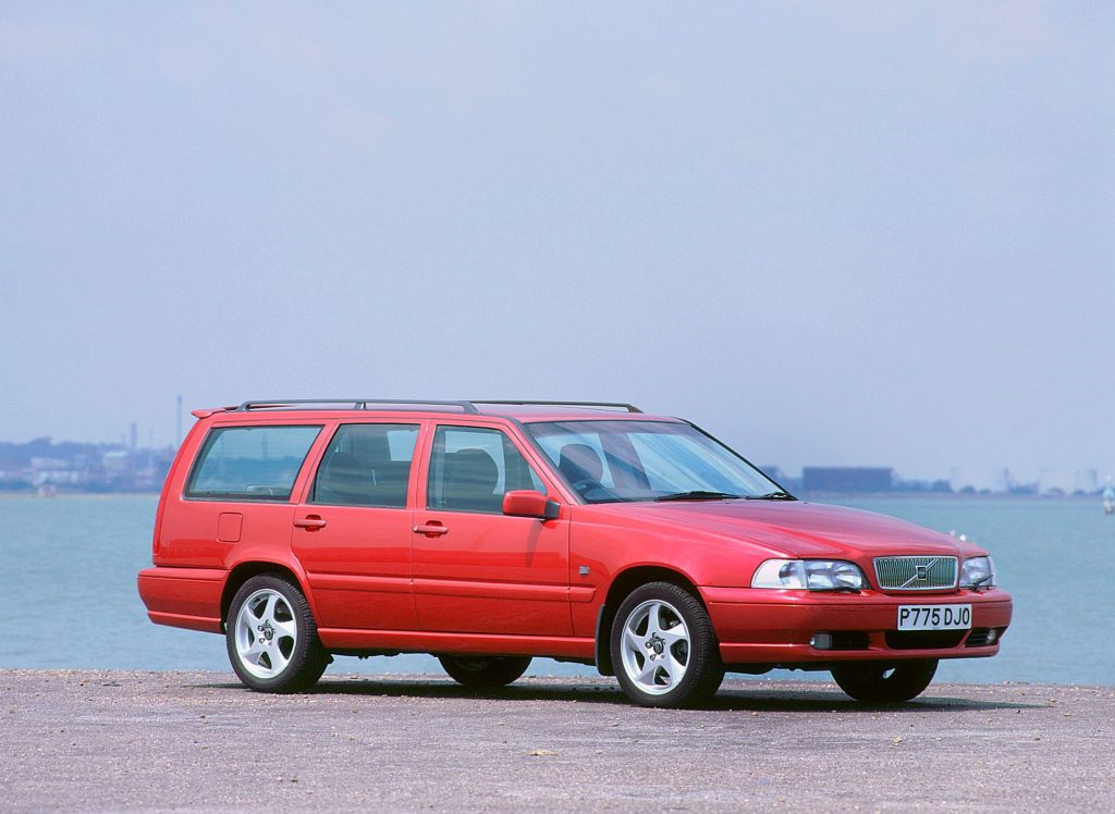 A red Volvo station wagon parked on a beach near the sea