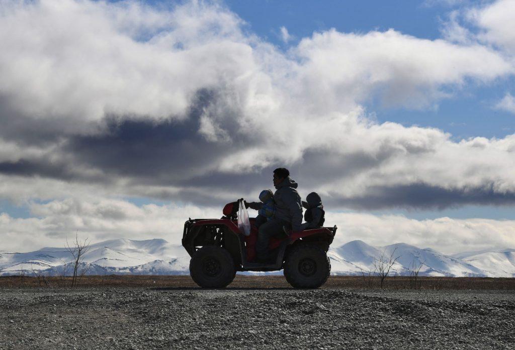 A family rides an ATV near the Yupic Eskimo town of Quinhagak on the Yukon Delta in Alaska on April 12, 2019