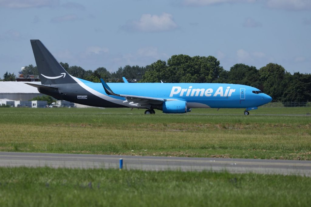 A blue, black, and white Amazon Prime Air Boeing 737 aircraft parked in an air field
