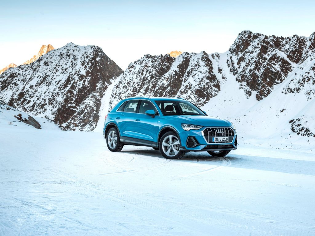 A teal Audi Q3 luxury SUV model parked in a snowy tundra