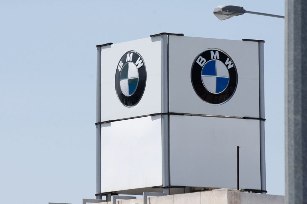 A white BMW marquee tower with BMW's logo shown on the two sides of the marquee visible with a clear sky in the background.