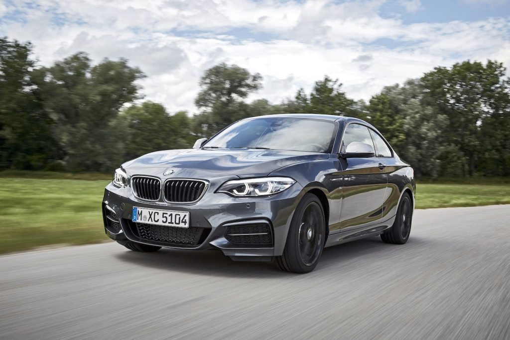 A grey BMW 2 Series driving past a grassy field and thick tree line