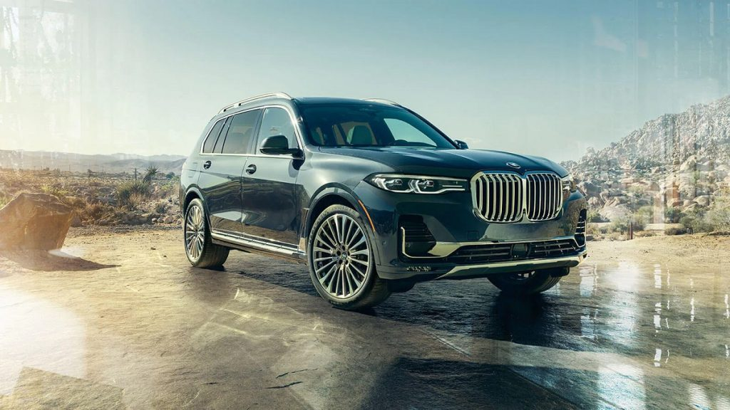 A black 2021 BMW X7 sits in a wooded clearing.