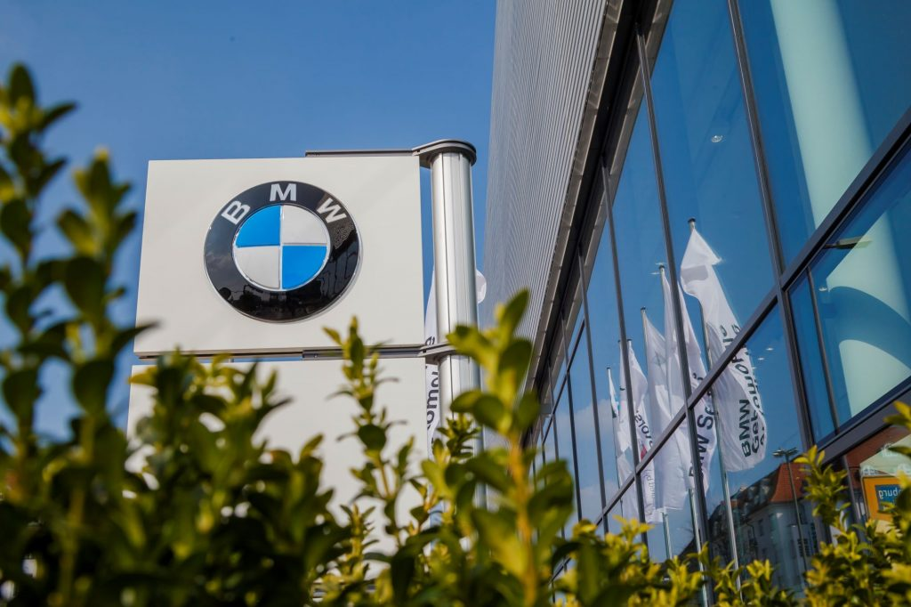 A BMW dealership marque is beside of a building with large windows with some blurred green shrubbery in the front.