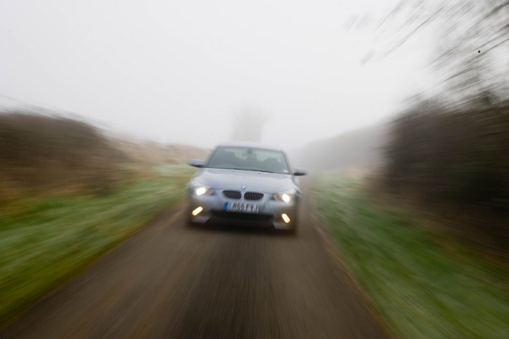 A BMW 5-Series car drives with its headlights illuminated on a country road in foggy weather