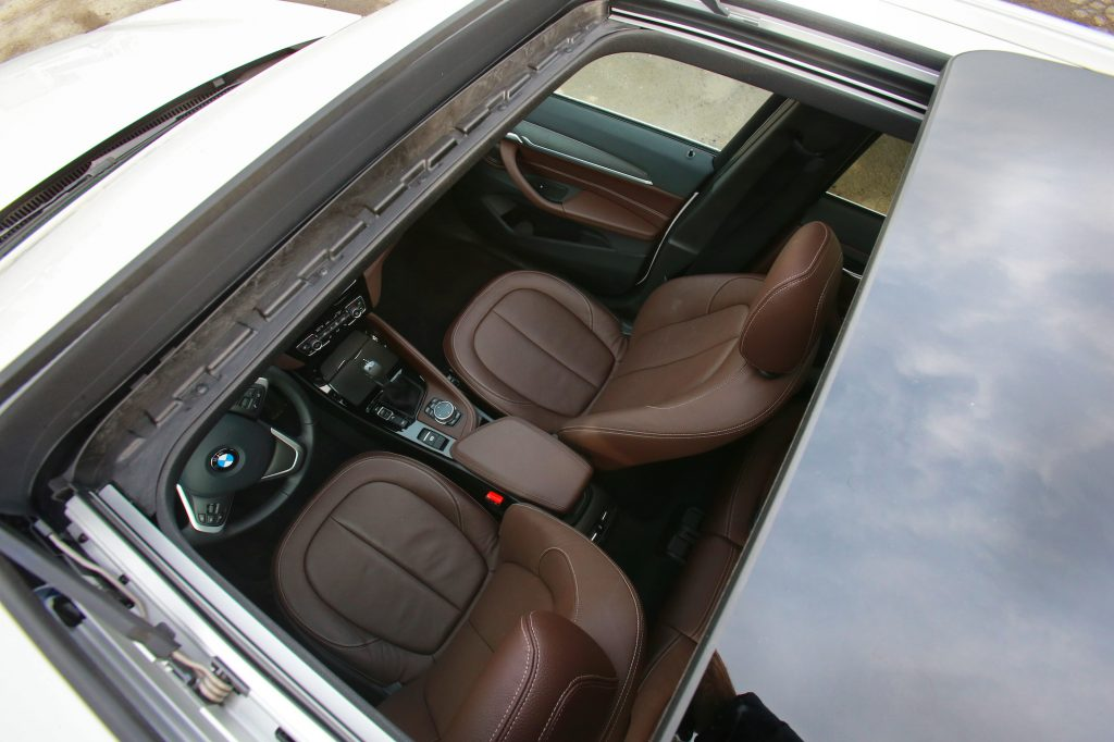 An overhead shot of a panoramic sunroof reveals the brown-leather interior of a 2016 BMW X1 xDrive 28i