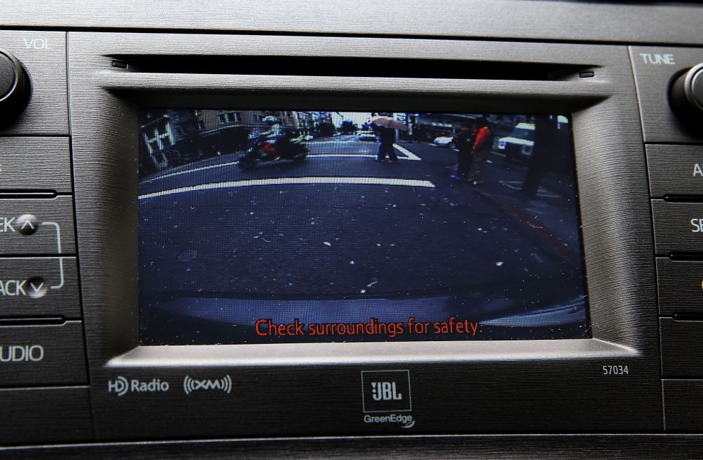 A infotainment screen with a backup camera view that has pedestrians and motorcyclists in the view of the camera with 'Check surroundings for safety' in red at the bottom of the screen.