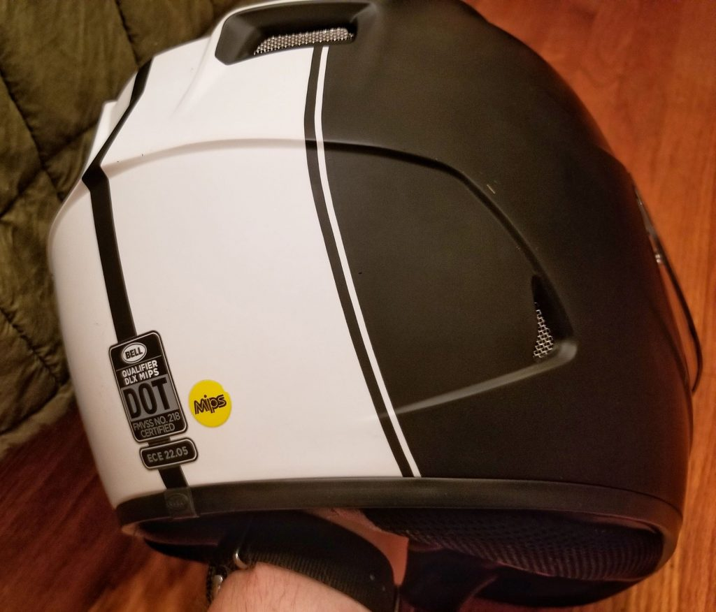 The rear view of a black-and-white Bell Qualifier DLX MIPS motorcycle helmet showing the DOT, ECE, and MIPS stickers