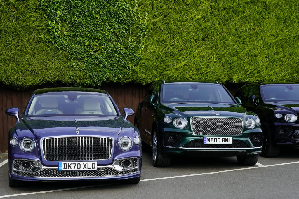 Bentley luxury cars lined up along a tall green hedge