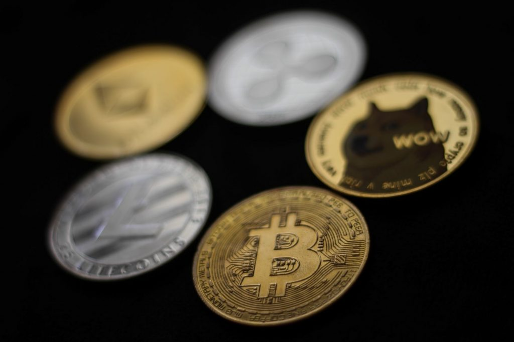 A visual representation of Bitcoin and other cryptocurrency placed next to each other on a black background