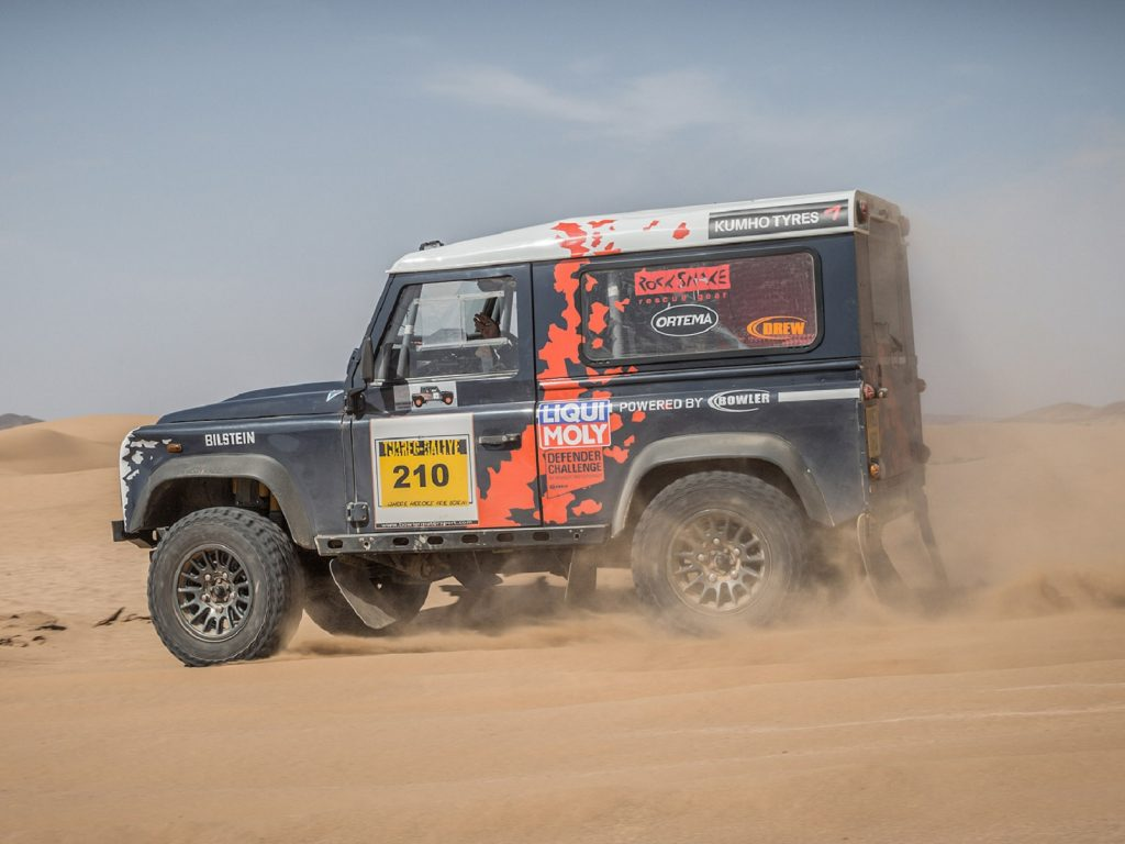 The side view of a classic Land Rover Defender converted to Challenge spec by Bowler racing in the desert