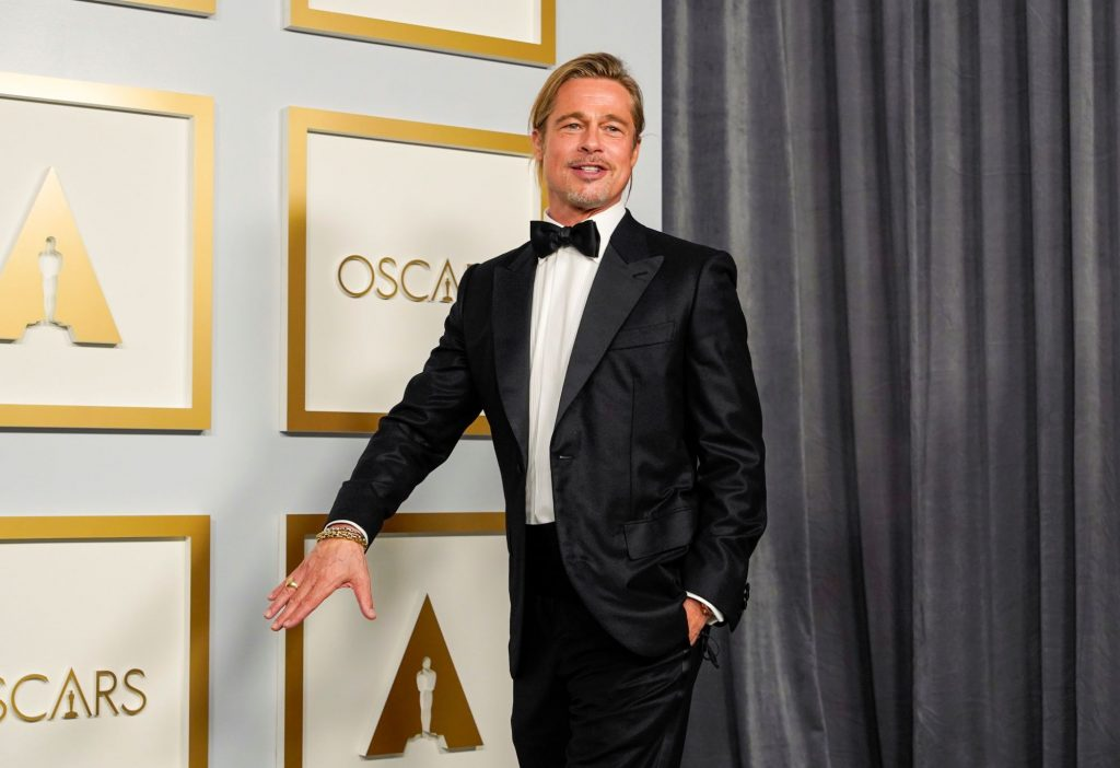 Brad Pitt walking in a black suit, white button up shirt and bow tie in front of a grey backdrop with gold references to the Oscars on it.