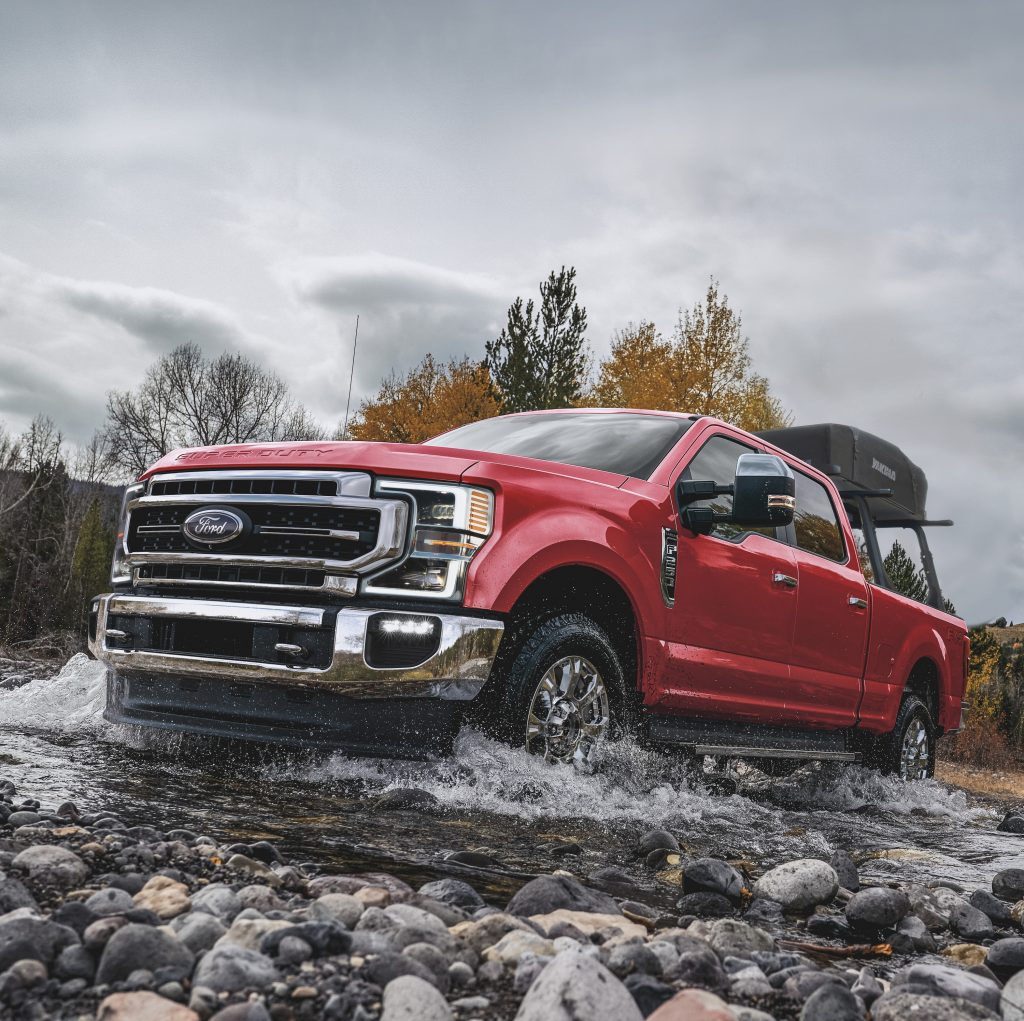 A red Ford F-Series truck plows its way through a rocky stream
