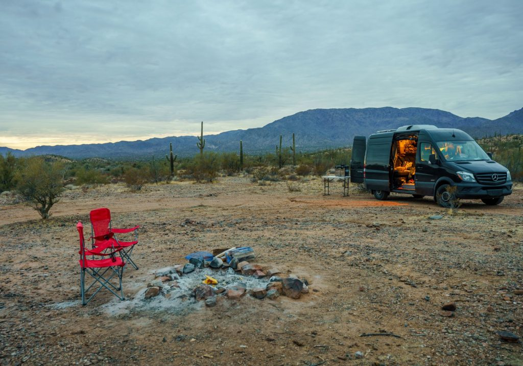 A camper van sits in a desert style area with a red chair sitting next to a campfire that recently went out.