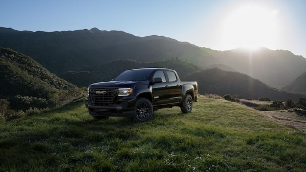 A black 2020 GMC Canyon sits atop a grassy hill.