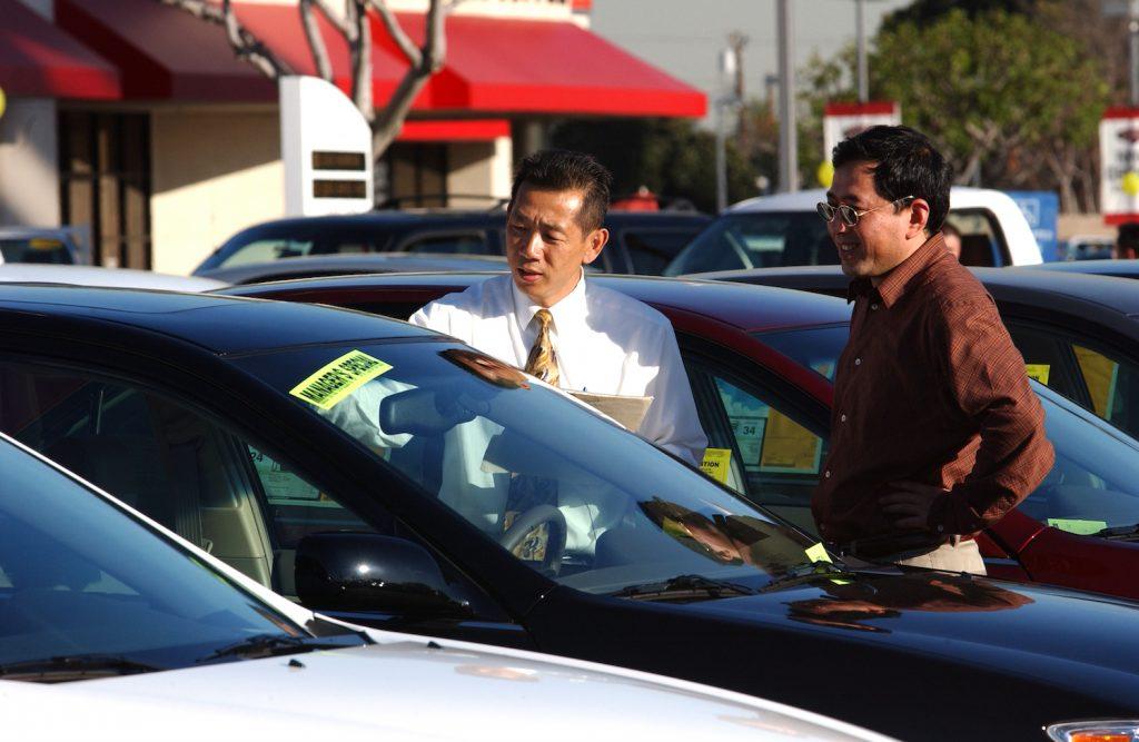 Two men on a car dealership lot