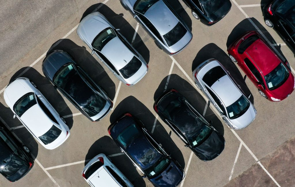 A group of cars in a dealership parking lot ranging in colors from black, red, and silver.