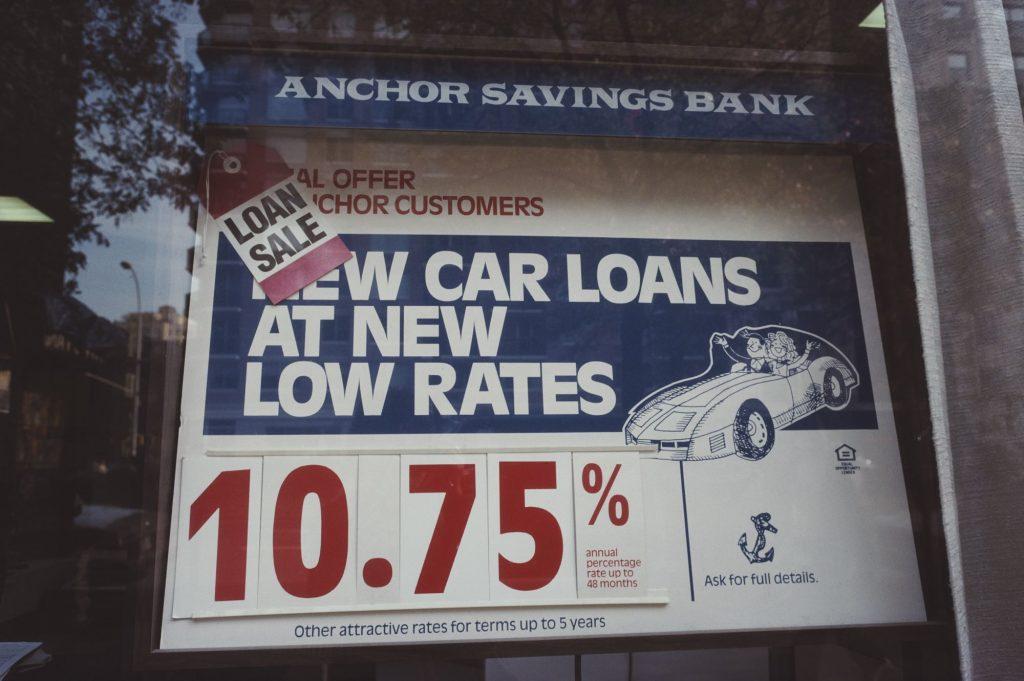 An Anchor Savings Bank with a car loans sign window