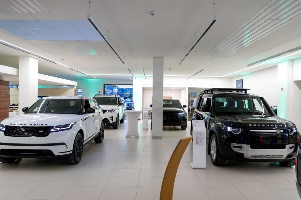 Picture of the inside of a car dealership with four Land Rovers, two on the right that are black and two on the let that are white, against a background of white walls, a wall with screens and a white column in the center.