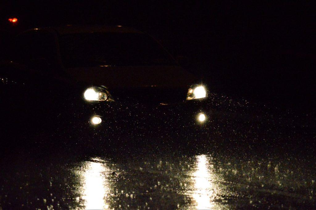 A pair of car headlights driving through darkness