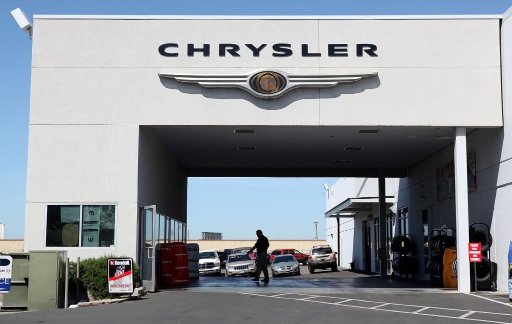 A Chrysler Service Bay with the Chrysler logo at the top and a person standing in the middle hosing off the ground.