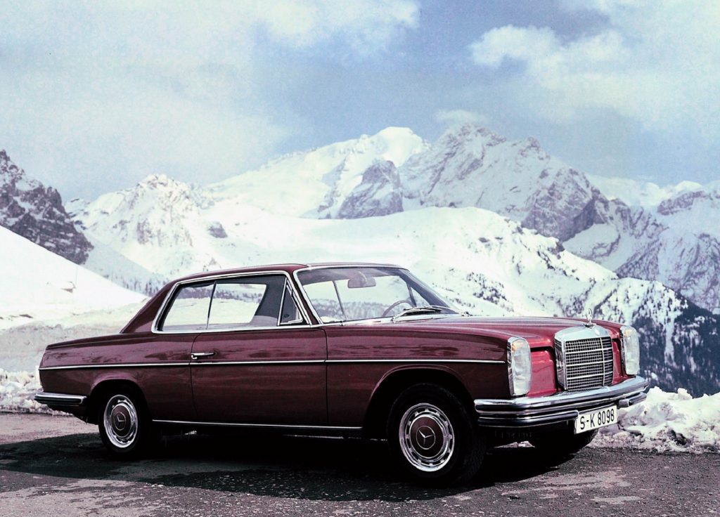 A red 1967 Mercedes 'W114' 250C coupe in the snow-covered mountains