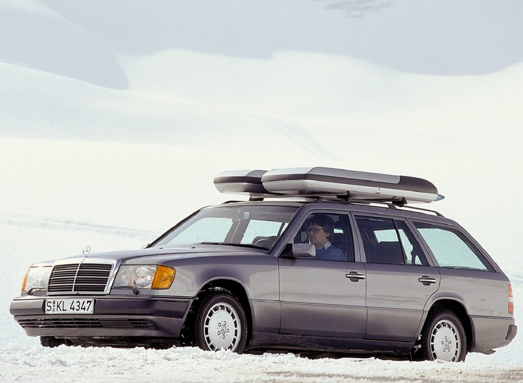 A silver 1988 Mercedes E-Class Estate with roof boxes on a snow-covered mountain