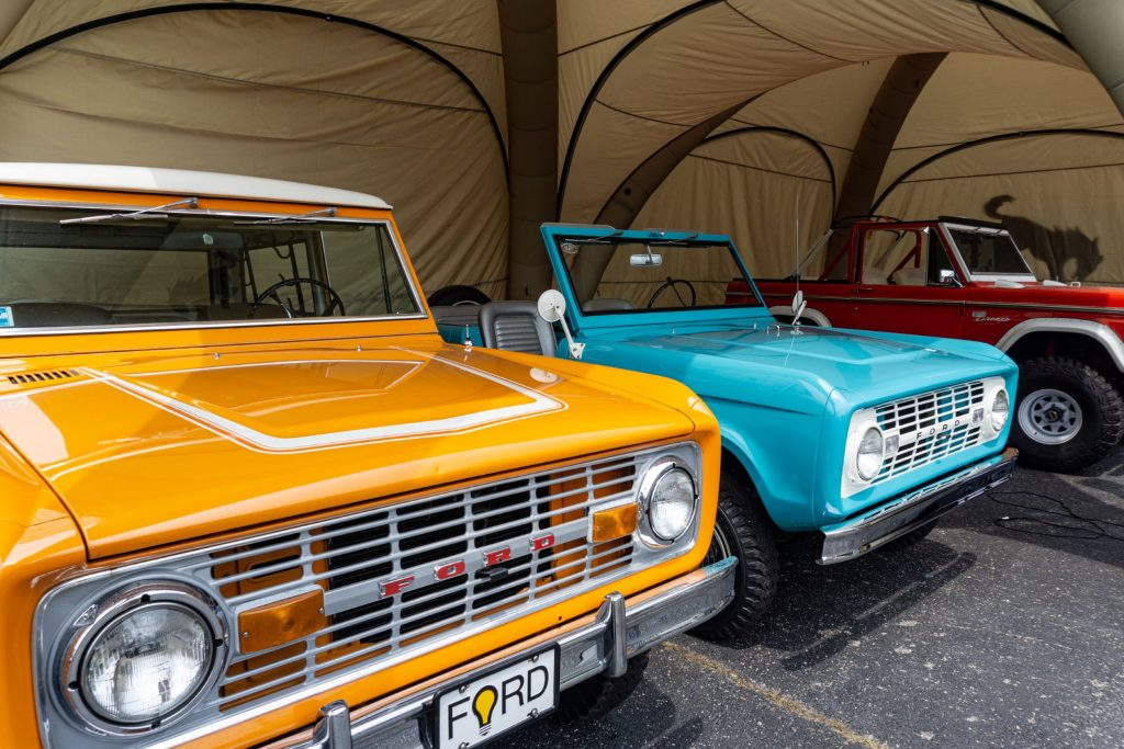 An orange, turquoise, and a red-and-white classic Ford Bronco under a tent outside the 2021 Chicago Auto Show