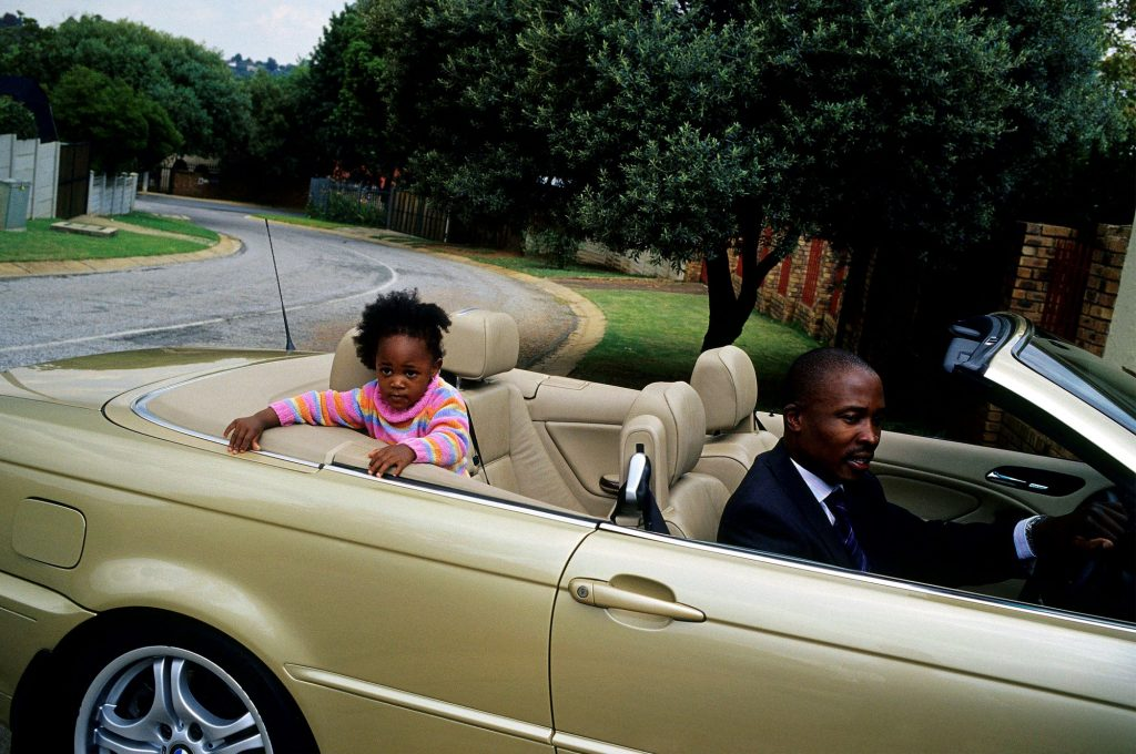 A father driving a gold convertible with his daughter in the back seat
