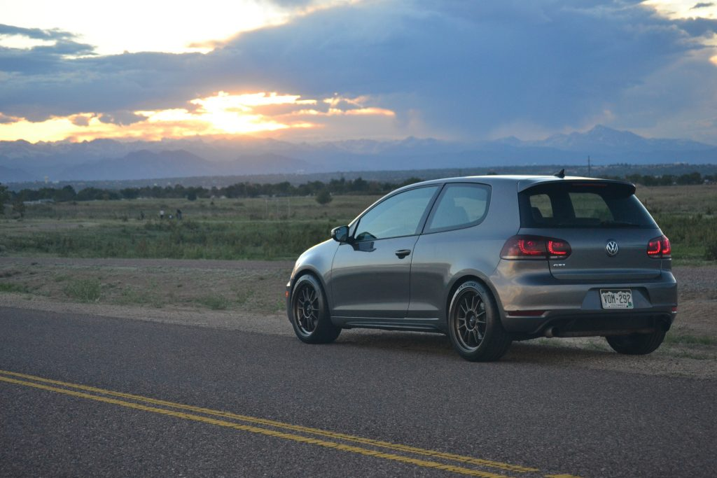 A gray Volkswagen GTI at sunset photographed from the rear 3/4.