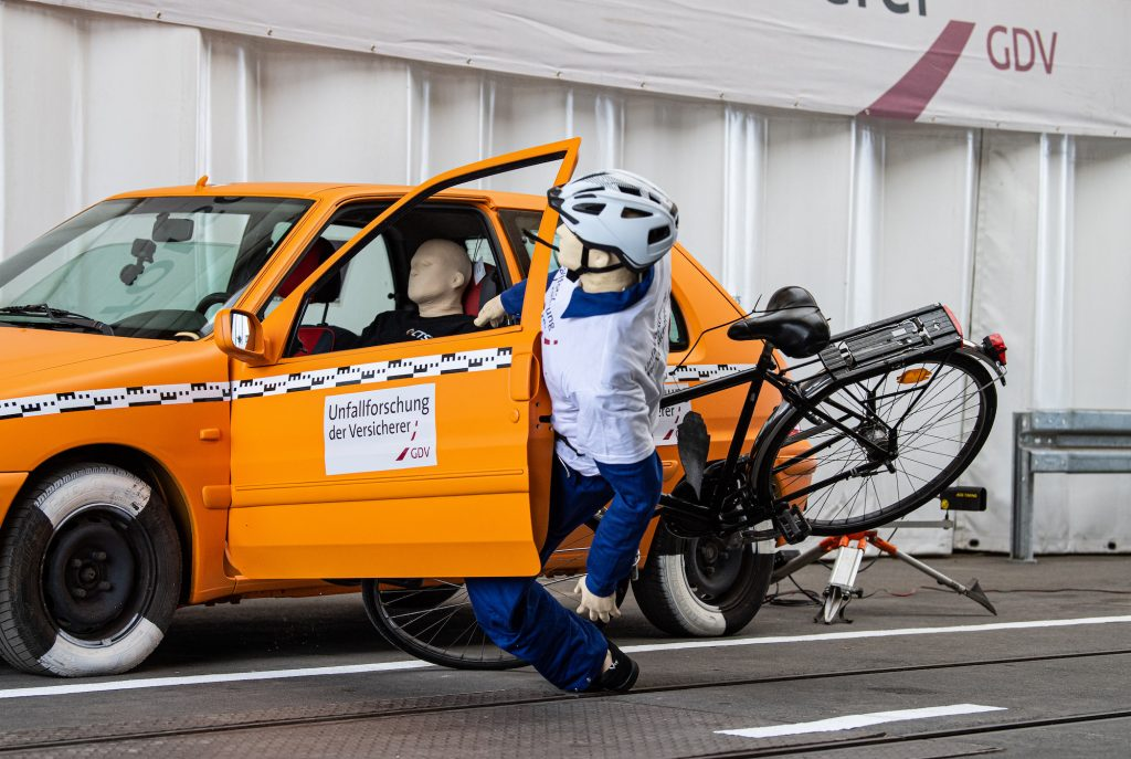 In a crash test conducted by the insurers' accident researchers, a crash test dummy on a bicycle crashes into an open door of a parked car - a so-called dooring accident