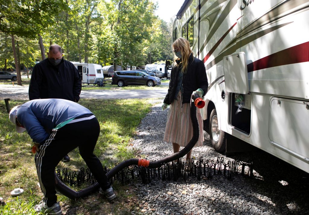 A group of campers dumping sewage water out from an RV