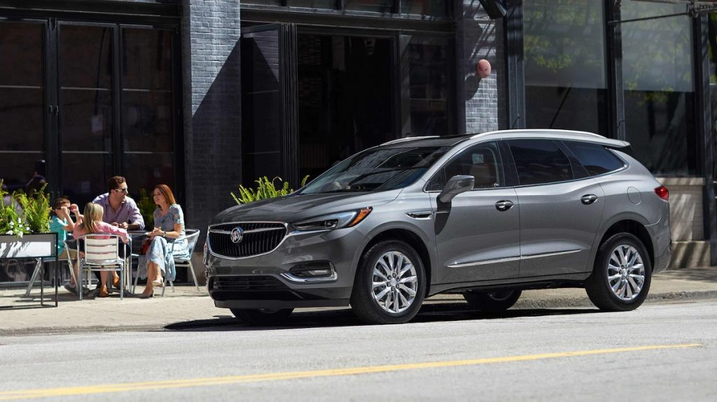 A gray 2021 Buick Enclave parked outside of a restaurant.