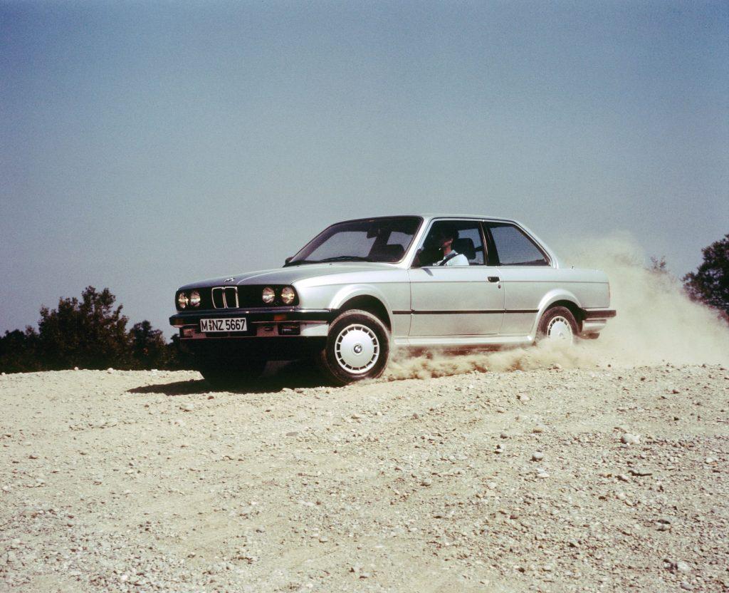 A silver E30 BMW 325iX sliding through gravel