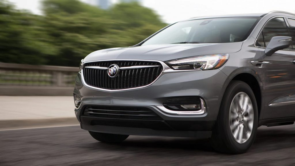 The front of a gray 2021 Buick Enclave driving down a street.