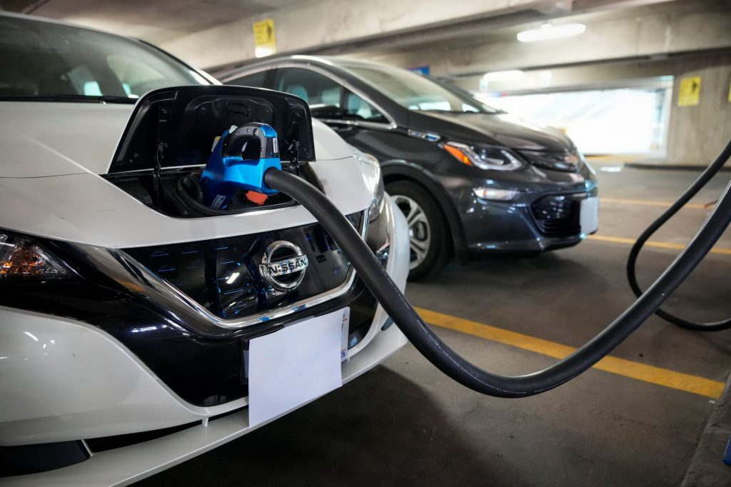A white Nissan Leaf EV plugged into an electric charging station in a parking garage