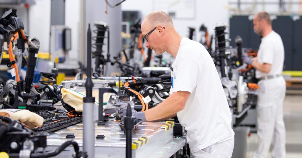 Volkswagen employees wire the battery on a line for the VW ID.3 during a press tour of Volkswagen's Transparent Factory.