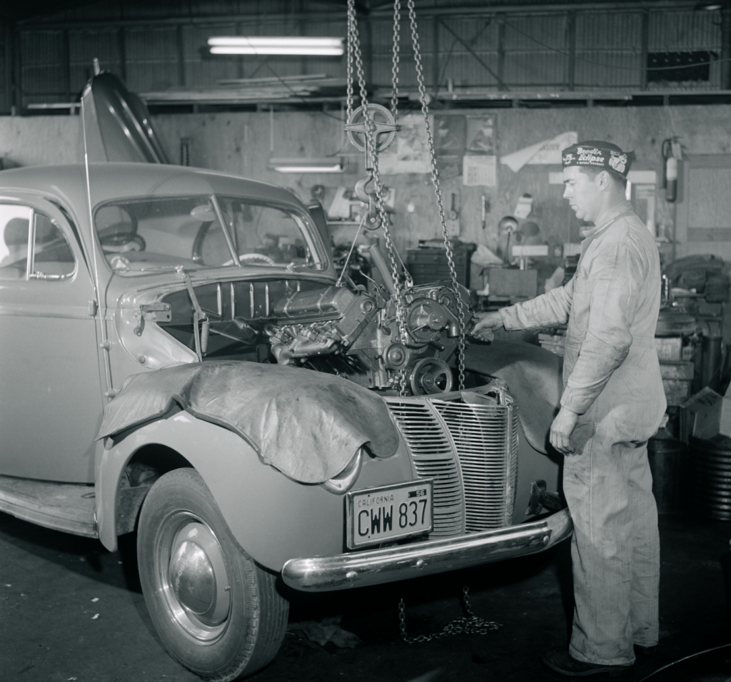 mechanic pulling engine out of a 1940 Ford