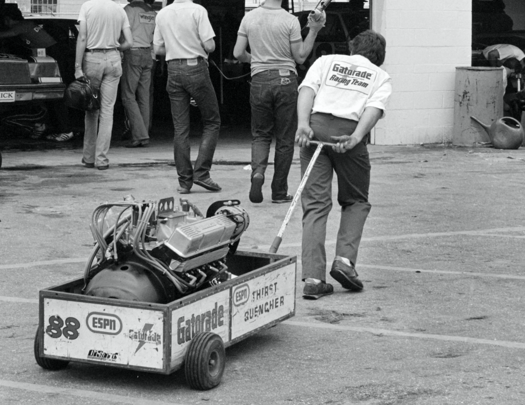 man hauling an engine in a cart