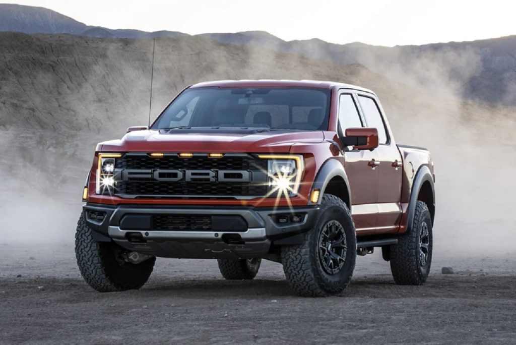 A red 2021 Ford F-150 on a gravel road.