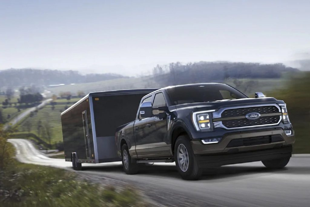 A blue 2021 Ford F-150 pulls a truck uphill.