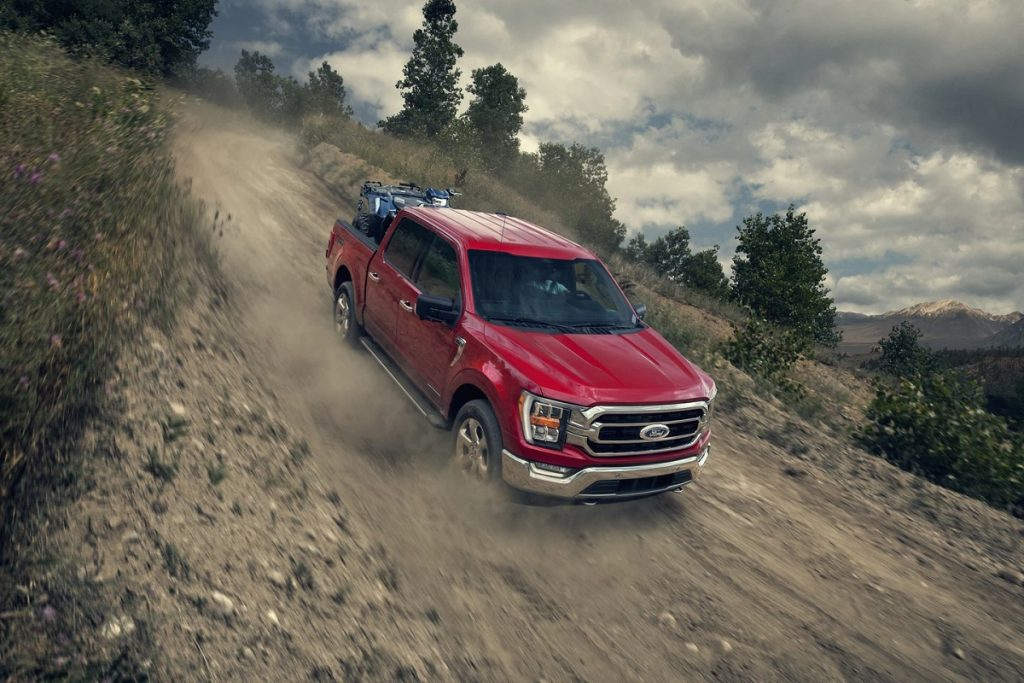 A red 2021 Ford F-150 drives down a dirt hill.