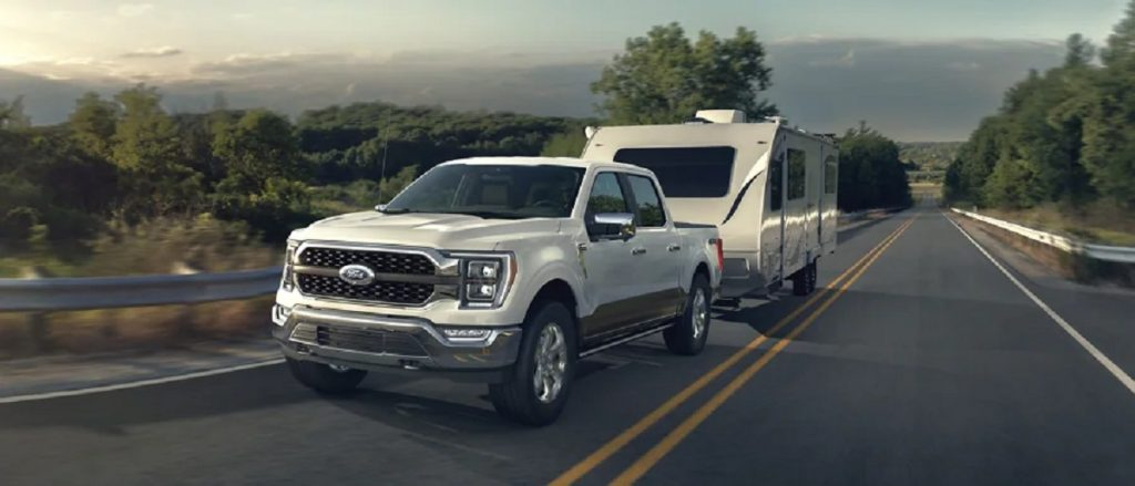 A white 2021 Ford F-150 tows a trailer on the highway.