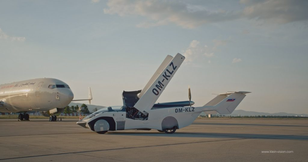 An AirCar sits on a runaway with its wings up.