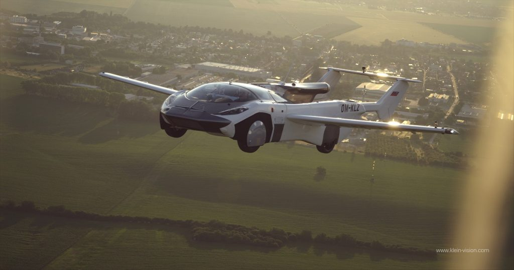 A car with wings flies high above the ground.