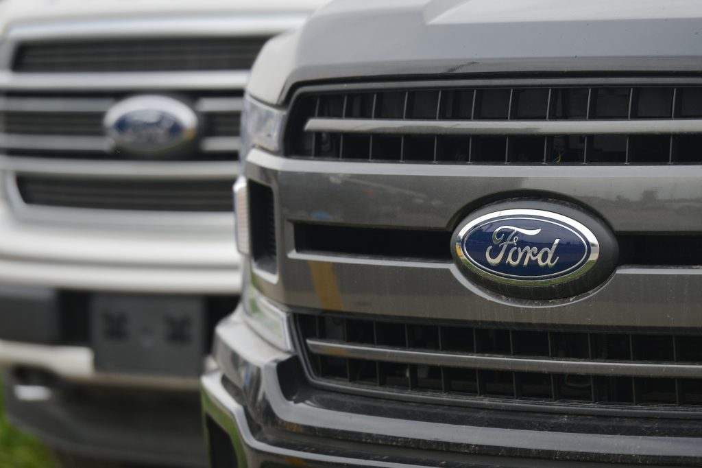 Ford logos on the grilles of two pickup trucks